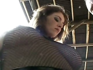 Amazing brunette in fishnet top gets pussy fucked by hunks on the table