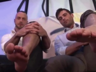 Super-hot office workmates demonstrating large feet on camera
