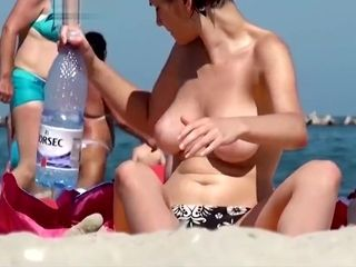 Super-sexy buxomy exhibitionist ultra-cutie heads bra-less on the beach to show her XXL tits!